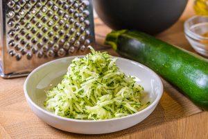 ズッキーニはチーズおろしなどで荒くすりおろしておく。 (千切りスライサーで代用可。包丁で細い千切りや薄切りにして入れてもOK。ただし大根おろし器でおろすと水っぽくなることがあるので、水気を軽く絞ってから入れる)